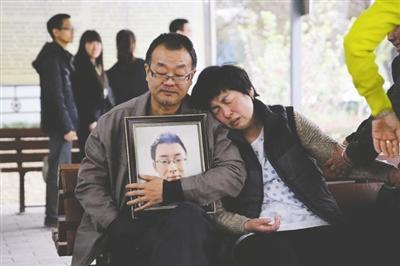 魏则西的父母怀抱他的遗像,悲伤不能自已 图据财新